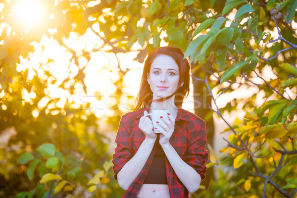 beautiful young woman with cup of coffee on the wonderful trees  Stock photo © Massonforstock