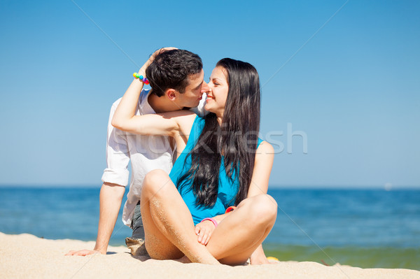 photo of cute couple sitting on the beach and kissing on the won Stock photo © Massonforstock