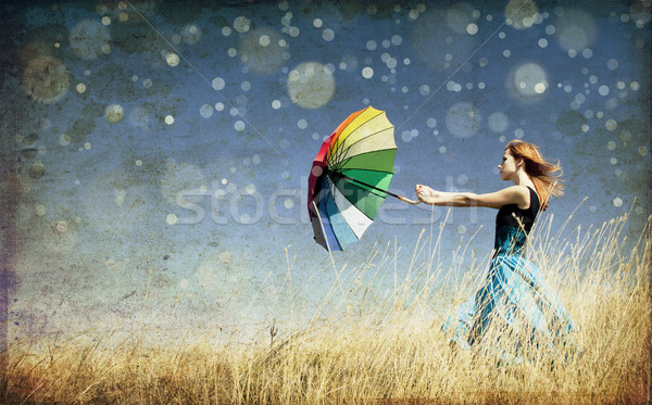 Redhead girl with umbrella at windy grass meadow. Photo in old c Stock photo © Massonforstock