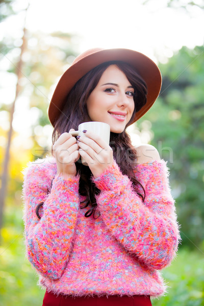 photo of beautiful young woman with cup of coffee standing in th Stock photo © Massonforstock