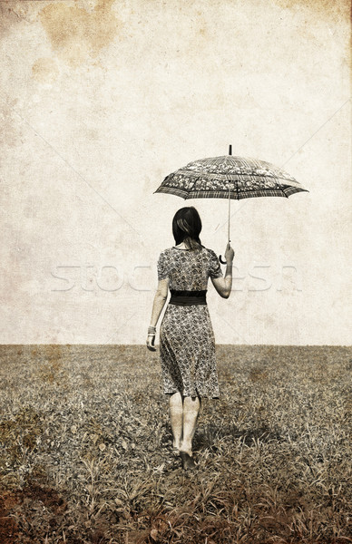 Girl with umbrella on field. Photo in old image style.  Stock photo © Massonforstock