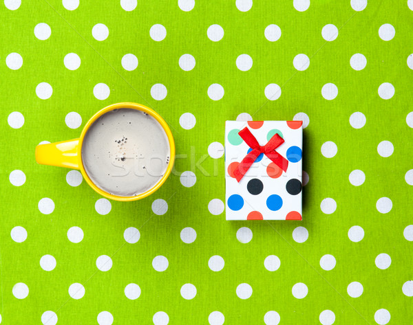 photo of cup of coffee and cute gift on the wonderful green dott Stock photo © Massonforstock