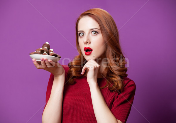 photo of beautiful young woman with plate full of chocolate cand Stock photo © Massonforstock