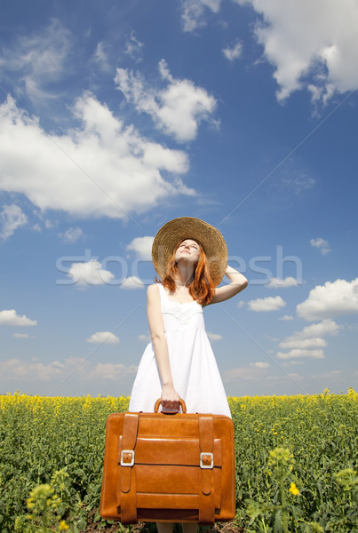 Redhead enchantress with suitcase at spring rapeseed field. Stock photo © Massonforstock