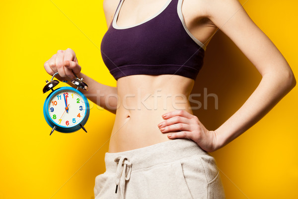 photo of perfect slim female body with alarm clock in the hand o Stock photo © Massonforstock