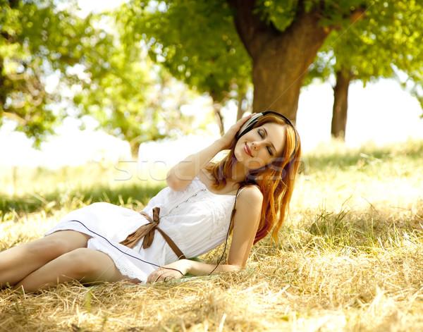 Stock photo: Beautiful redhead girl with headphones at garden.