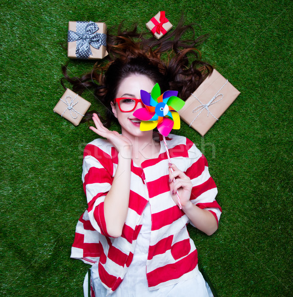Portrait of a young styled redhead woman with pinwheel toy prese Stock photo © Massonforstock