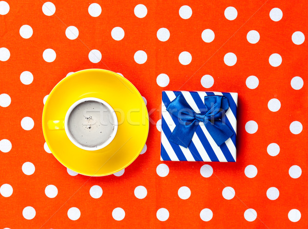 photo of cup of coffee and cute gift on the wonderful red dotted Stock photo © Massonforstock