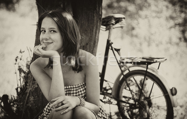 Beautiful girl sitting near bike and tree at rest in forest.  Stock photo © Massonforstock