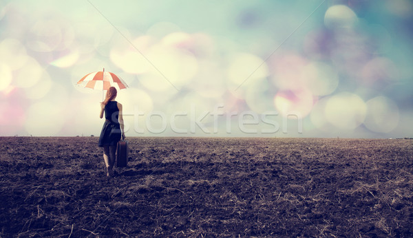 Redhead girl with umbrella and suitcase at windy field Stock photo © Massonforstock
