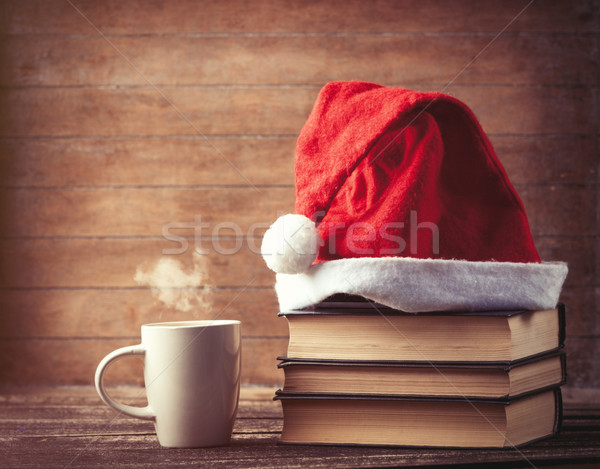 Santas hat over books near hot cup of coffee or tea  Stock photo © Massonforstock