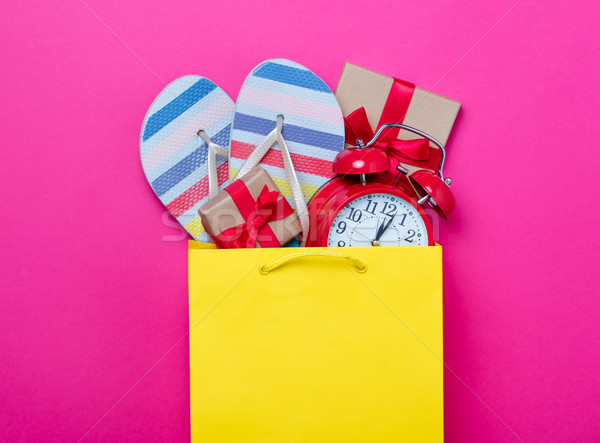 cute gifts, alarm clock and cool sandals in shopping bag and coo Stock photo © Massonforstock
