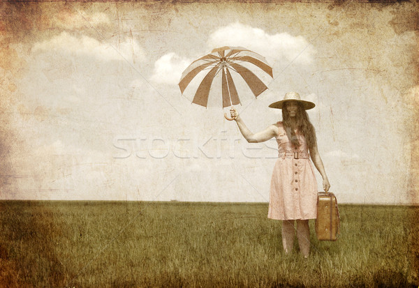 Brunette enchantress with umbrella and suitcase at spring field. Stock photo © Massonforstock