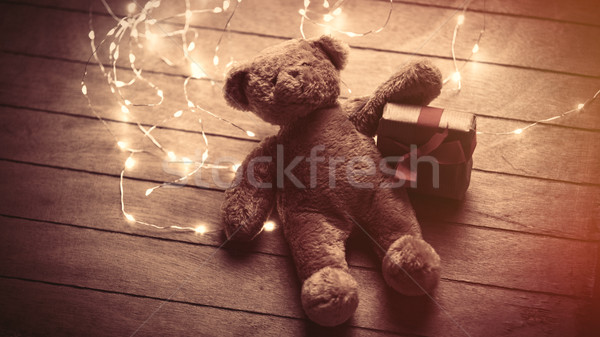 cute fluffy teddy bear with gift and bright garland on the wonde Stock photo © Massonforstock