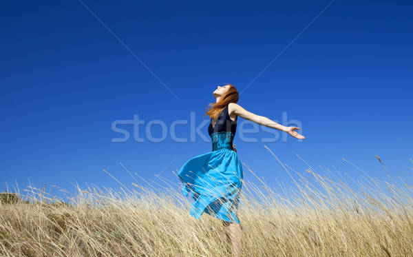 Stock photo: Redhead girl at windy field.