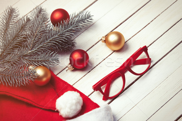 Santas hat and christmas bubbles with red glasses Stock photo © Massonforstock