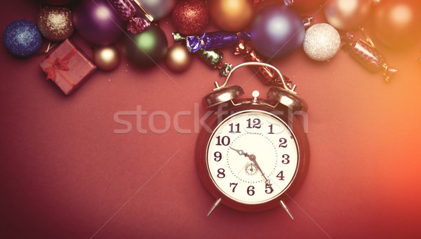 Alarm clock and christmas toys on red table. Stock photo © Massonforstock