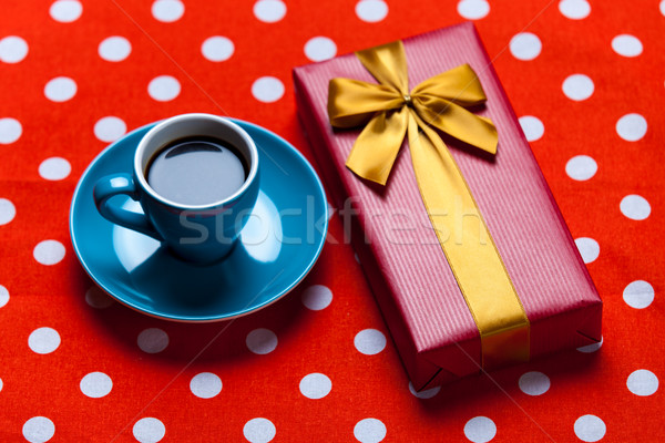 photo of blue cup of coffee and cute gift on the red dotted back Stock photo © Massonforstock