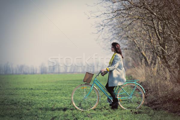 Gyönyörű fiatal nő ül bicikli csodálatos zöld Stock fotó © Massonforstock