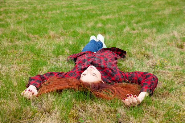 beautiful young woman lying on the field and relaxing on the won Stock photo © Massonforstock