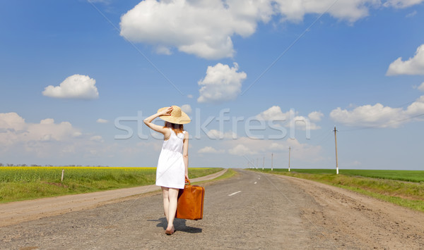 Lonely girl with suitcase at country road. Stock photo © Massonforstock
