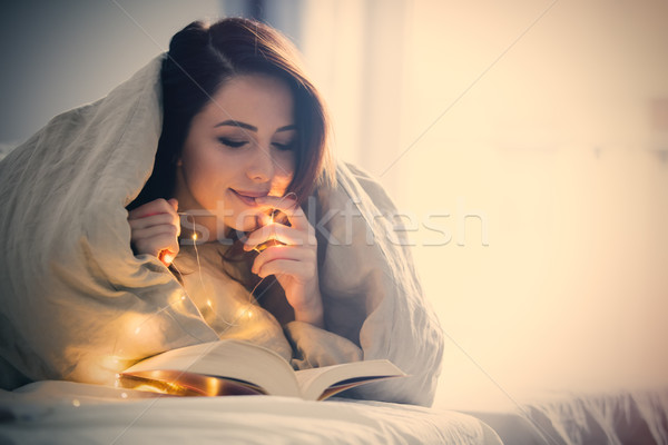 woman with fairy lights and book Stock photo © Massonforstock