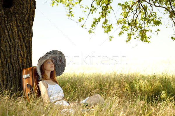 Redhead girl in hat sitting near tree at countryside. Stock photo © Massonforstock