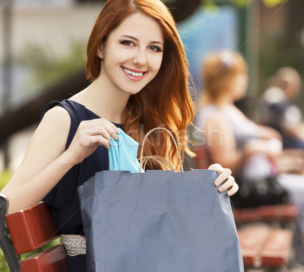 Style redhead women sitting on the bench with shopping bags Stock photo © Massonforstock