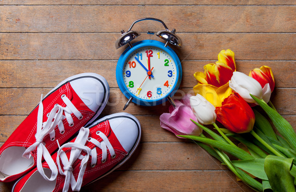 bunch of tulips, red gumshoes and clock lying on the table Stock photo © Massonforstock