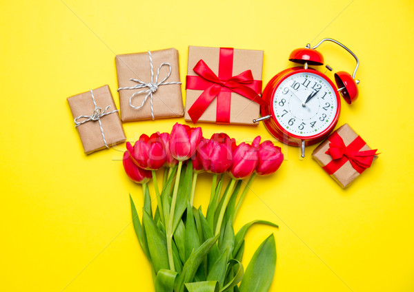 bunch of red tulips, alarm clock and beautiful gifts on the wond Stock photo © Massonforstock