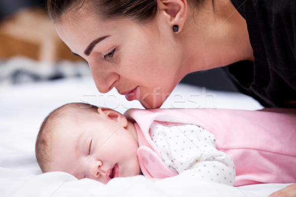 beautiful young mother going to kiss her sleeping baby lying on  Stock photo © Massonforstock