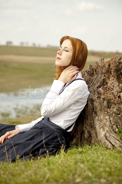 Girl sitting at green grass near stump. Stock photo © Massonforstock