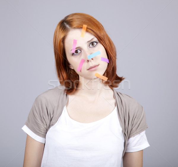 Confused red-haired businesswomen with notes on face. Stock photo © Massonforstock