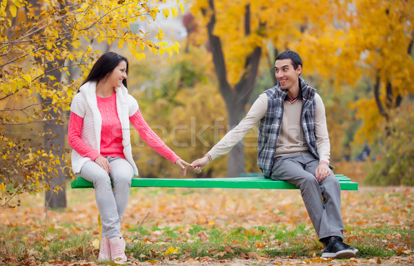 photo of cute couple sitting on the bench and holding hands on t Stock photo © Massonforstock