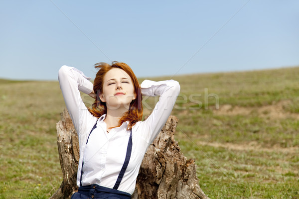 Girl sitting at green grass near stump. Stock photo © Massonforstock