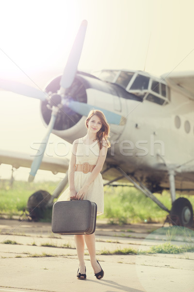 Lonely girl with suitcase at near airplane.  Stock photo © Massonforstock