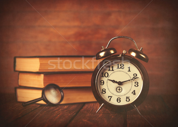Books with loupe and retro alarm clock  Stock photo © Massonforstock