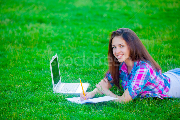 beautiful young girl lying on the field with laptop and copybook Stock photo © Massonforstock