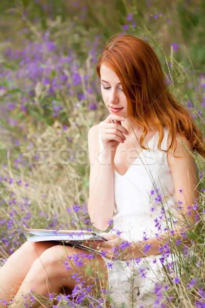 photo of beautiful young woman with copybook sitting on the gras Stock photo © Massonforstock