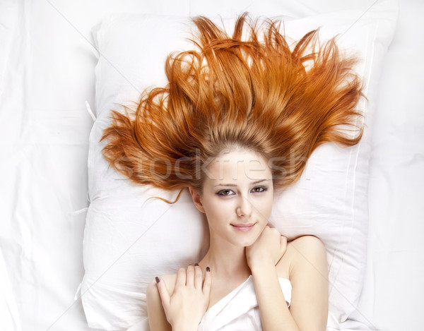 Stock photo: Fashion red-haired girl in the bedroom.