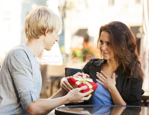 The young man gives a gift to a young girl in the cafe Stock photo © Massonforstock