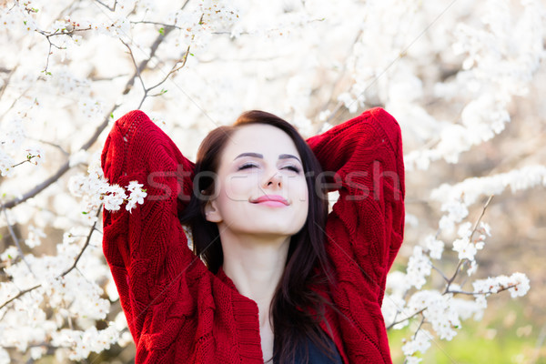 beautiful young woman standing in front of wonderful blooming tr Stock photo © Massonforstock