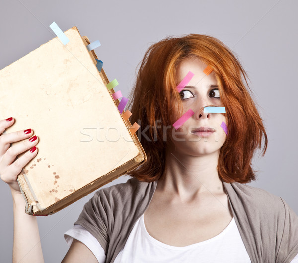 Red-haired businesswoman with book and notes on face. Stock photo © Massonforstock
