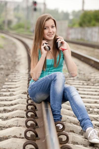 Stock photo: Teen girl with headphones at railways.