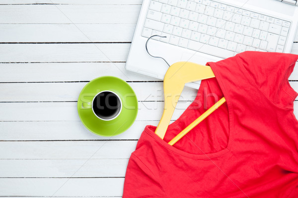 Cup of coffee and hanger with red dress near computer  Stock photo © Massonforstock