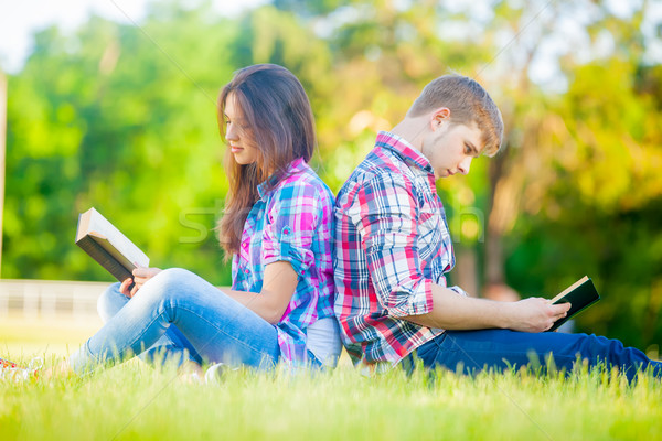 beautiful cute couple sitting on the field and reading their boo Stock photo © Massonforstock