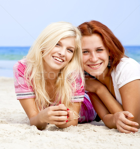 Two girl friends lying down at the beach. Stock photo © Massonforstock