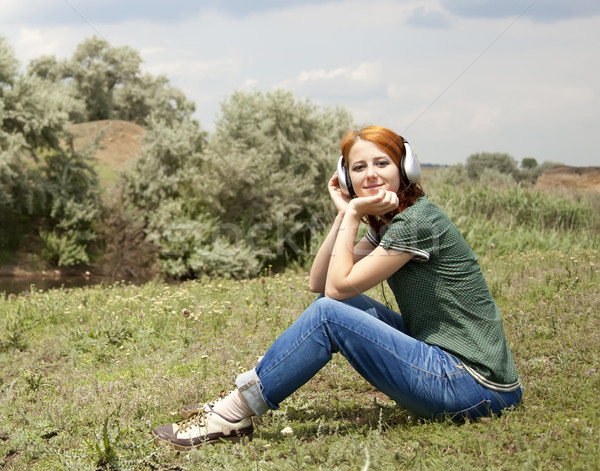 Young fashion girl with headphones at grass in spring time. Stock photo © Massonforstock