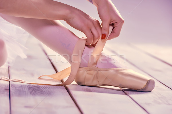 Stock photo: Professional ballerina putting on her ballet shoes.