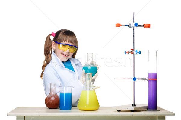 Little girl as chemist doing experiment with chemical fluid in the laboratory Stock photo © master1305